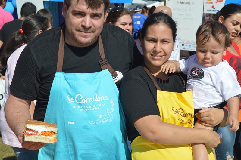 Pedro Almarza, junto a su esposa e hijo, exhibiendo el sandwich que preparó.