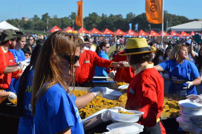 Las chicas de Tigo ayudando en el servicio de la paella.