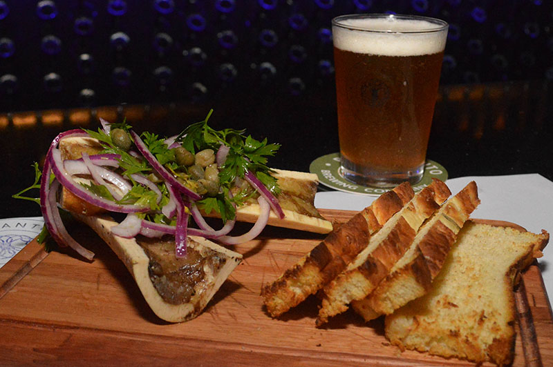 Caracú a la cuchara con toques de cebolla morada, perejil y acompañado de tostadas de focaccia. Maridado con una cerveza Preludio.