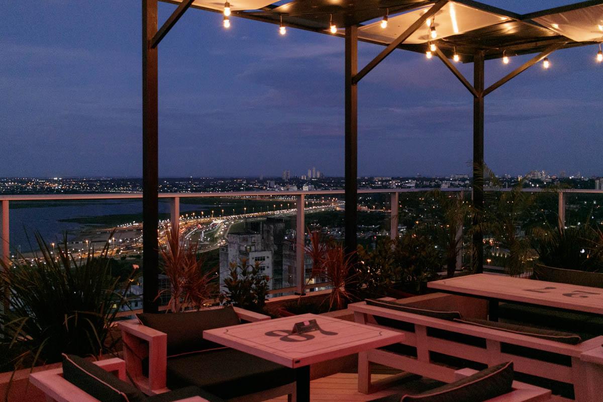 Comienza a anochecer y la terraza del Negroni regala esta vista. Allá abajo la avenida costanera comienza a delinearse gracias a su iluminación. La bahía está siendo tragada por la oscuridad que acerca la noche. Y las mesas y sillas esperar recibir a los clientes.