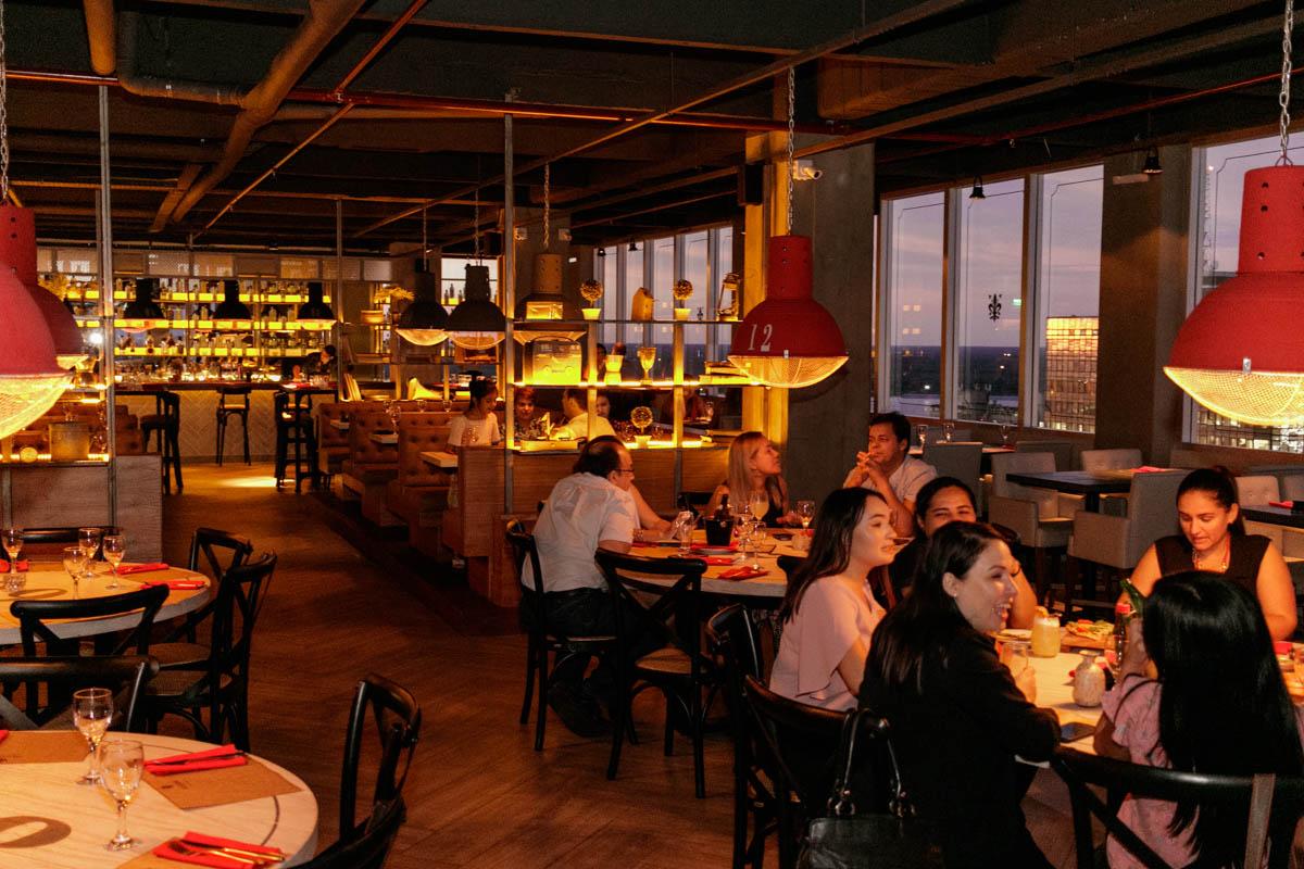 El típico tono amarillento y anaranjado que caracteriza a los ambientes de los locales Negroni. Al fondo la barra del bar.
