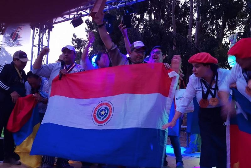 Leyzman Salim levanta el trofeo conquistado por el equipo paraguayo, a su derecha, Hugo Adorno también realiza un gesto de victoria, mientras que una chilena pareciera que está extendiendo nuestra bandera.
