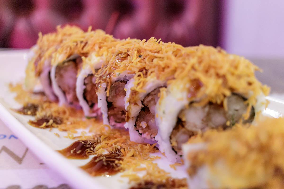 Este rollo de sushi se llama La Gran Muralla China. Lleva camaron y pescado apanados, queso crema, cebollita, aguacate, salsa teriyak, mayones de naranja y miel. Puede verse que tiene una delgada lámina de arroz y mucho más proteína.