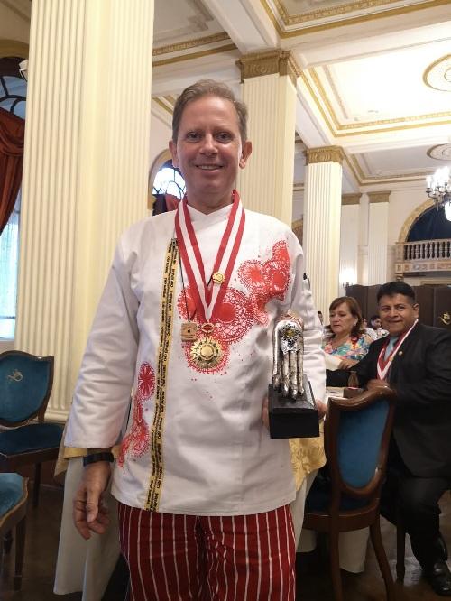 Peyton Gwynn luciendo la medalla y el trofeo recibido en Lima, por su trabajo de investigación acerca de la influencia africana en la gastronomía paraguaya.