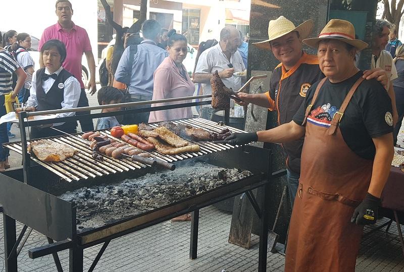 Dos parrilleros con lo que quedó del asado que preparon sobre la calle Palma en la Galería de la Senatur. Fue para promocionar el Dia del Parrillero ocasión en que harán la sopa paraguaya más larga.