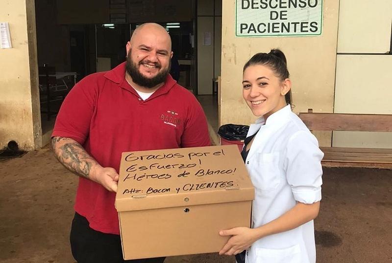 Thiago Antunez, chef de Bacon Burgers, haciendo entrega de las hamburguesas en uno de los hospitales.