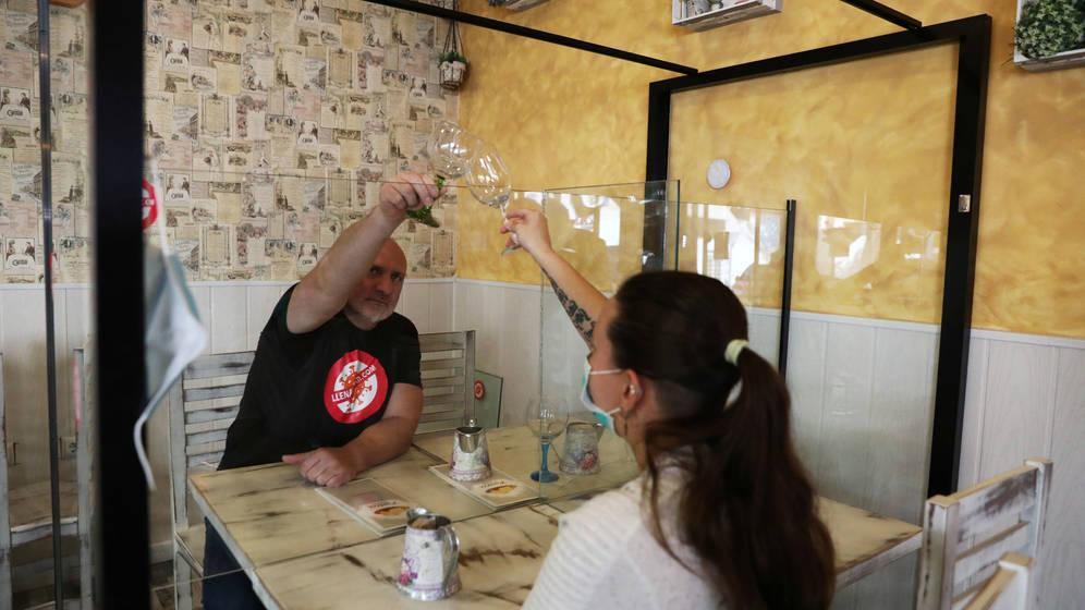 En esta imagen tomada en un restaurante de España, muestra el distanciamiento con una mampara que aquí no se exige pero se recomienda.