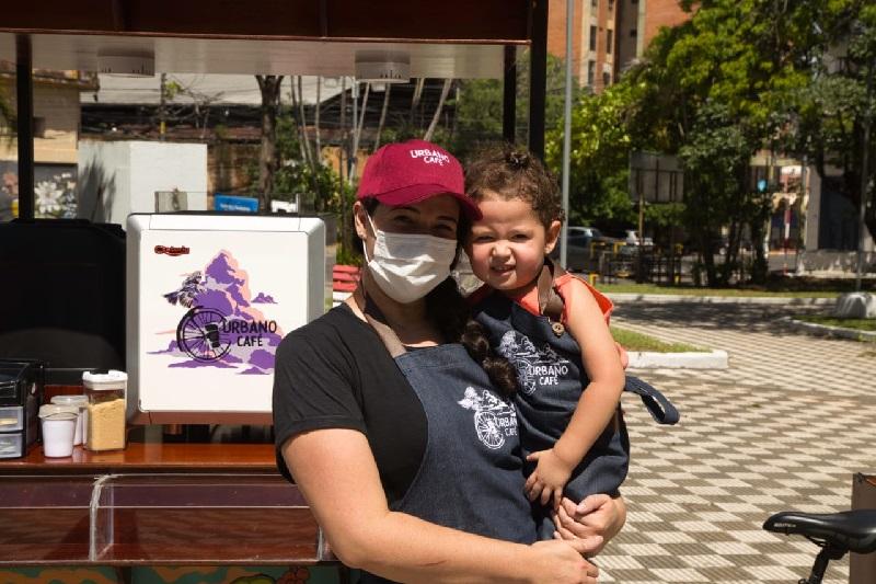Alicia González junto a su pequeña hija Zoe frente al carrito de su cafetería móvil que recorre los espacios públicos con la idea de democratizar el consumo de café y revitalizar el uso de las plazas.