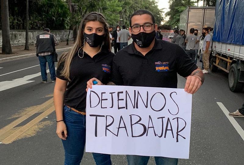 Germán Buttner, propietario de Kombistro, una hamburguesería gourmet, durante la protesta realizada ayer en inmediaciones de Mburicha Roga. Aparece junto a su novia Camila Riveros.