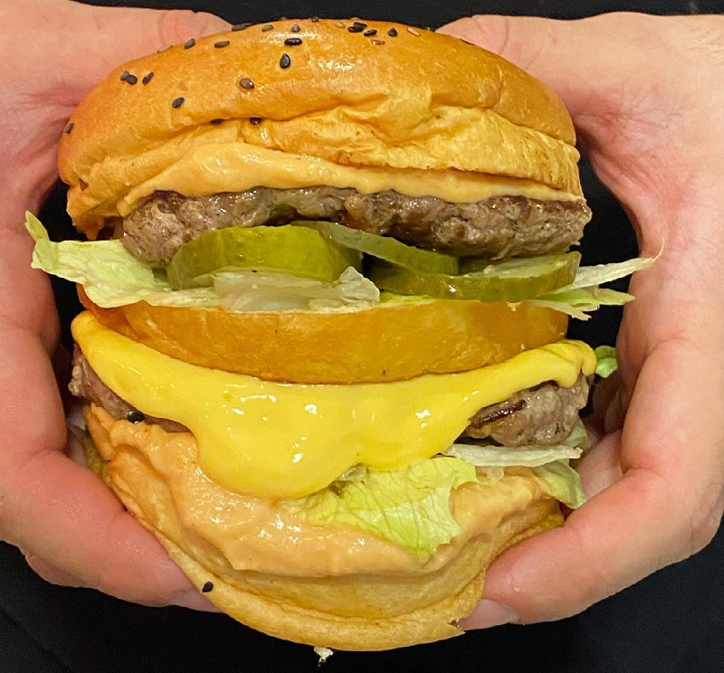 """Una hamburguesa que lleva doble entrecostilla, con lechuga repollada, pepinillos, queso Chedar y una salsa secreta. """"Nuestro tributo a la legendaria burger del payaso!! """", según Bruno Brusquetti."""