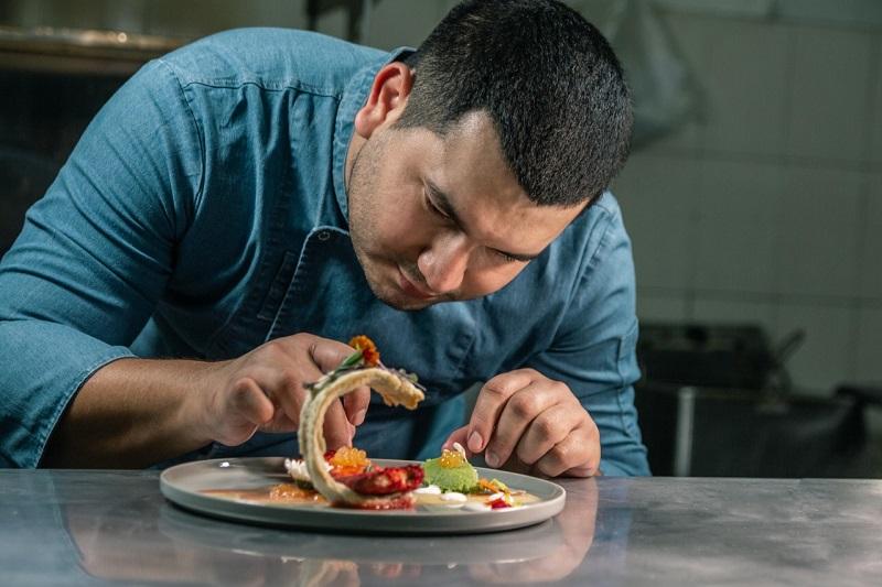 El chef Juan Avila preparando uno de sus platos con pescado. Su restaurante El Dorado es ya todo un éxito en Villa Morra.