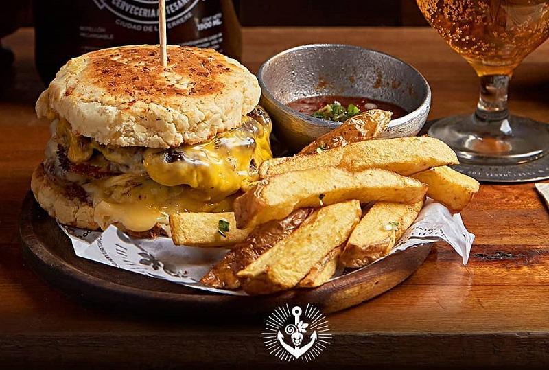 Una hamburguesa que sería común y corriente si no fuera porque lleva chipa en vez de pan.